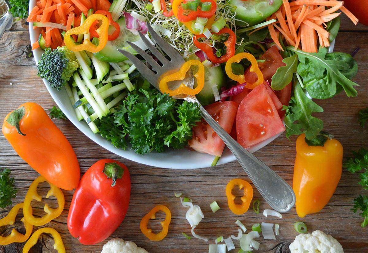 Lautasella värikkäitä vihanneksia ja haarukka.