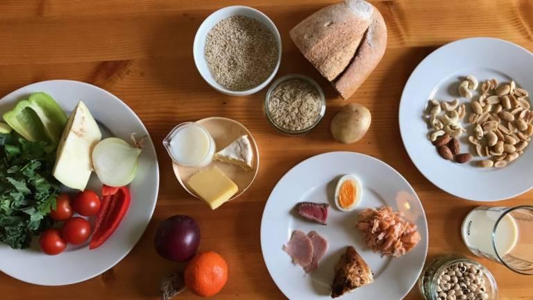 Puupöydällä lautasia, joissa vihanneksia, siemeniä, leipää ja muuta ruokaa.
