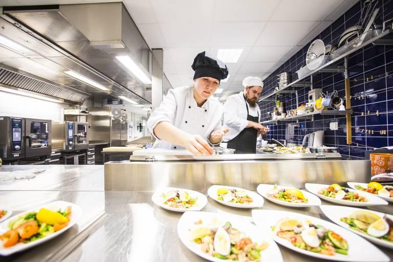 Restonomiopiskelijat valmistavat ruokaa opetuskeittiössä.